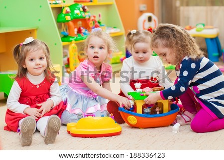 Little girls playing with toys in the playroom