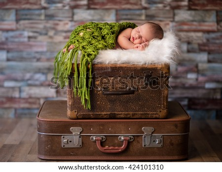Little newborn baby peacefully sleeping on rustic  suitcases, travel or newborn photography concept - stock photo