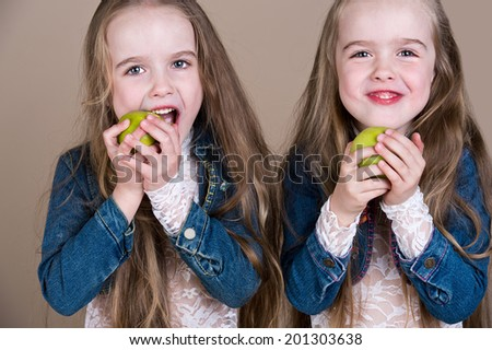 little twin sisters eats apples - stock photo