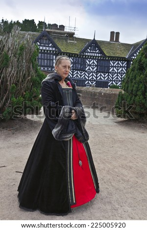 LIVERPOOL, UK - SEPTEMBER 29, 2014: Portrait of an unidentified female volunteer excursion guide at the Speke Hall dressed in Tudor time attire in the mannor house grounds. - stock photo