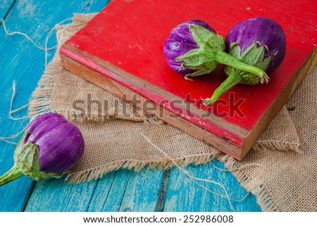local organic  eggplants  set  on red wooden cutting board and blue table  - stock photo