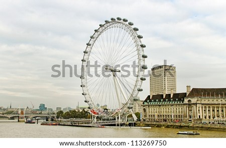 LONDON - OCTOBER 16: View of London Eye,which is the tallest ferris wheel in Europe, along the bank of the Thames River on October16, 2011 in London. - stock photo