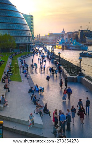 LONDON, UK - APRIL15, 2015: South walk of river Thames in sun set light. View includes a lot of walking people and London hall building - stock photo