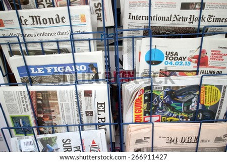 London, United Kingdom - April 02, 2015: International and Foreign Language newspapers including Le Monde, USA Today and Le Figaro on display in a rack outside a store.