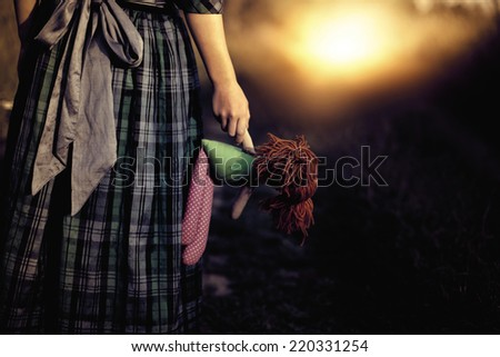 Loneliness - the girl with the doll goes to the light - stock photo