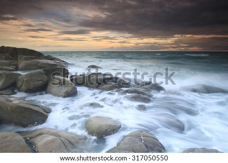 Long exposure for soft focus of the wave against rock beach , Long Exposure of Sunset at the sea,Larn hin khao , Rayong,Thailand , sunset at White rock beach , Rayong