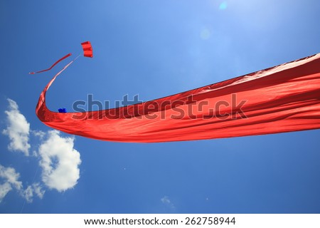 Long red kite against a vivid blue sky. - stock photo