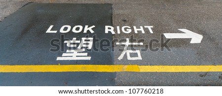 """look right"" sign on a street in hong kong, advising safety for pedestrians"