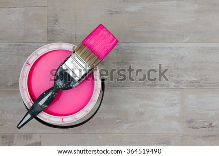 Looking down on a can of magenta Paint with a loaded brush stood on a shabby style wood floor - stock photo