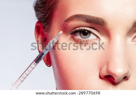 ?lose-up of a woman doing an injection under the eyebrow - stock photo