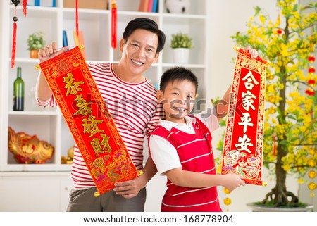 Ã?Â??lose up portrait of a father and his son holding red textiles with greetings for the New Year on the foreground  - stock photo
