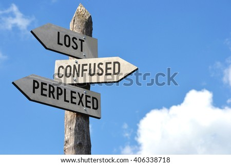 """""""Lost, confused, perplexed"""" - wooden signpost, cloudy sky - stock photo"""