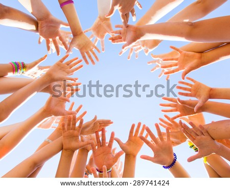 lot of children's hands reach for the sky forming a circle - stock photo