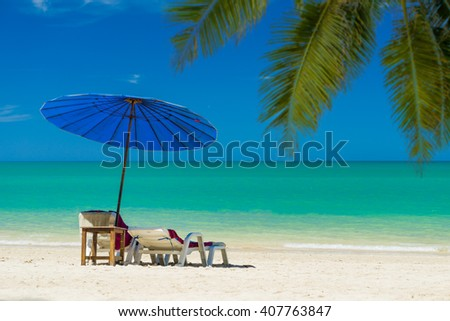 lounge chairs with sun umbrella on the tropical  beach