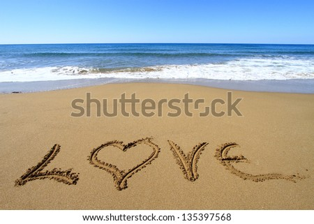 """Love"" written on golden sandy beach - stock photo"