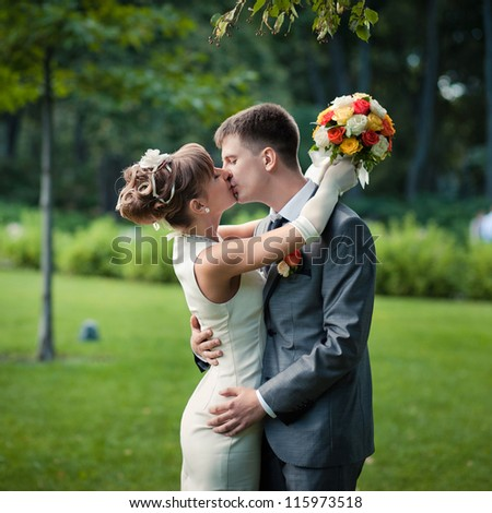 Lovely couple in love kissing each other on the day of the wedding they are even standing in the park outdoors - copyspace - stock photo