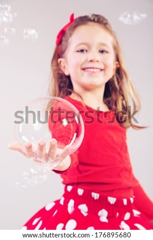 lovely little girl playing with soap bubbles - stock photo