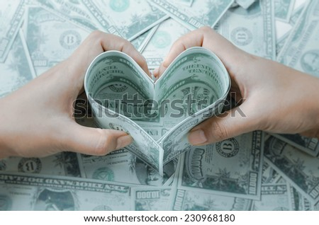 """Loving money"" concept. Heart made of few dollar papers. - stock photo"