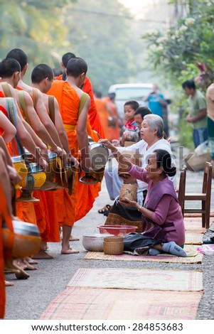 LUANG PRABANG, LAOS- APRIL 12, 2015 : Monks gathering morning alms in Luang Prabang.The tradition of giving alms to monks in Luang Prabang has been extended to tourists.