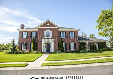 luxurious red brick house with green lawn - stock photo