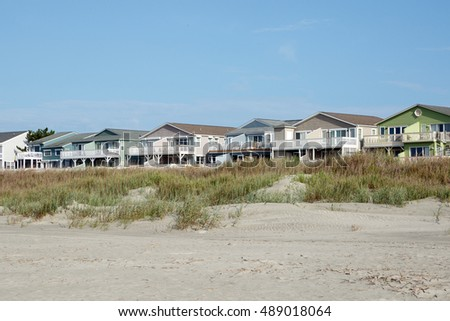 Luxury beach vacation houses across the green sand dunes, in Sunset Beach, North Carolina.