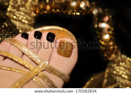 Luxury pedicure with black and gold lacquer on women's toes on the black and brilliant background. - stock photo