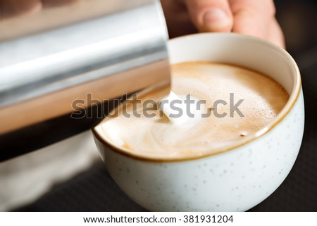 Macro process. Closeup shot of a milk being poured into the cup of cappuccino - stock photo