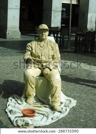 MADRID-MAY12: An unidentified street live statue entertainer performs for tourist as a live statue in cement make-up in historic site of Plaza Mayor, Madrid, Spain on May 12, 2015.  - stock photo
