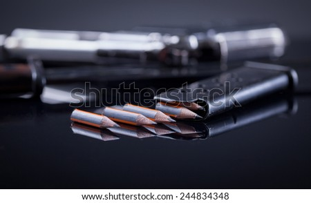 magazine knife, pen in the form of bullet and blurred gun in the background - stock photo