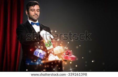 magician with magic Christmas  box,  performs the trick  - stock photo