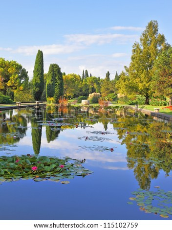 Magnificent Italian park at sunset. Smooth water of a pond reflects coastal cypresses and picturesque bushes