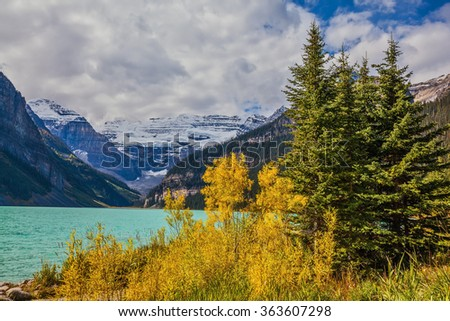 Magnificent Lake Louise with emerald water surrounded by glaciers.  A great sunny day. Rocky Mountains, Canada, Banff National Park - stock photo