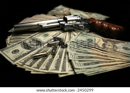 357 magnum handgun on a pile of money with bullets - stock photo