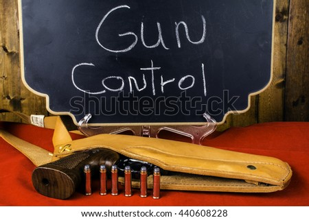 357 magnum revolver in leather holster with six bullets on red background in front of chalkboard reading gun control