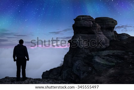 Majestic mountain scenery with the silhouette of a tourist,  starry sky and  northern lights
