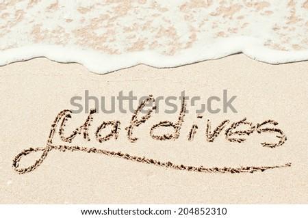 """Maldives"" written on the sandy beach - stock photo"