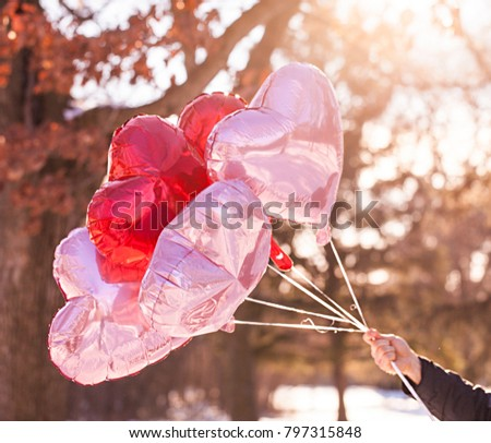 Male hand holding heart balloons. Valentine's day concept