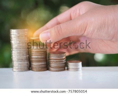 Male hand putting money coin stack growing business.Saving money concept