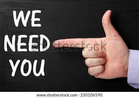 Male hand wearing a business shirt pointing at the phrase We Need You written on a blackboard - stock photo
