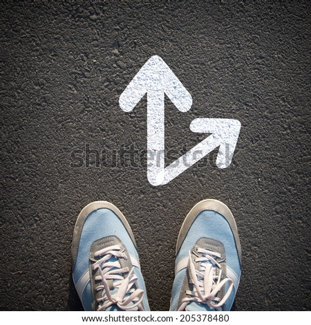 Male sneakers on the asphalt road with drawn direction arrows - stock photo