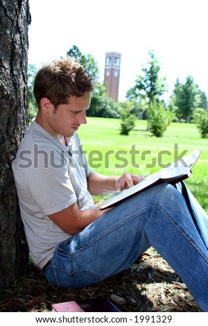 Male student reading by tree