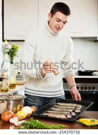 man adding spices in raw fish on roasting pan - stock photo