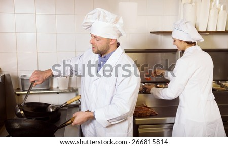 man and girl cooks cooking at professional kitchen in the take-away  restaurant - stock photo