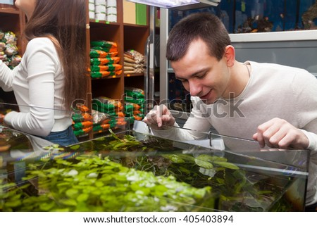 man and girl smiling and watching aquarium fish in shop