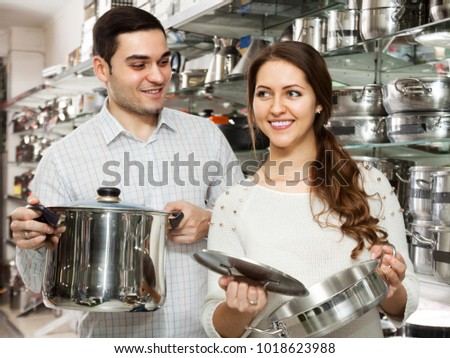 Man and woman buying pans in shop cookware