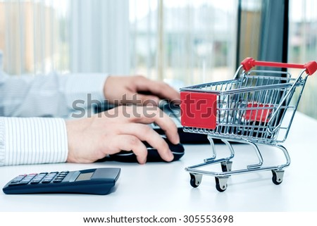 Man at the desk with his laptop and a miniature trolley. Conception of shopping on the internet. - stock photo