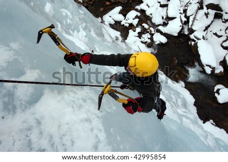 Man climbing a frozen waterfall - stock photo