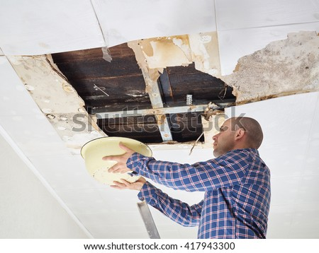 Man Collecting Water In basin From Ceiling. Ceiling panels damaged  huge hole in roof from rainwater leakage.Water damaged ceiling .   - stock photo
