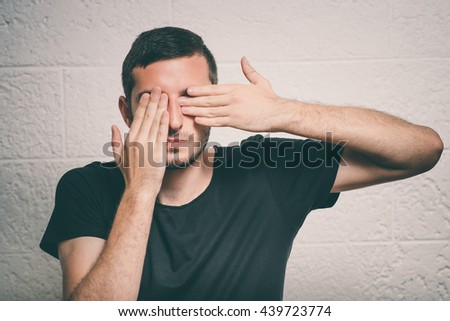 man covers his face by hand