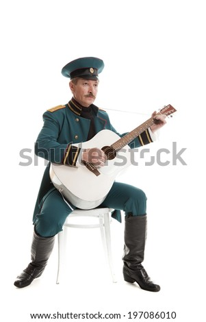 man dressed in a military uniform, playing guitar